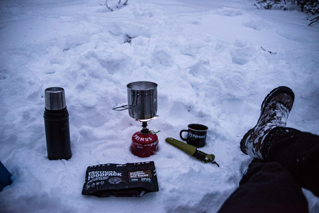 Smälta snö på stormkök vintercamping