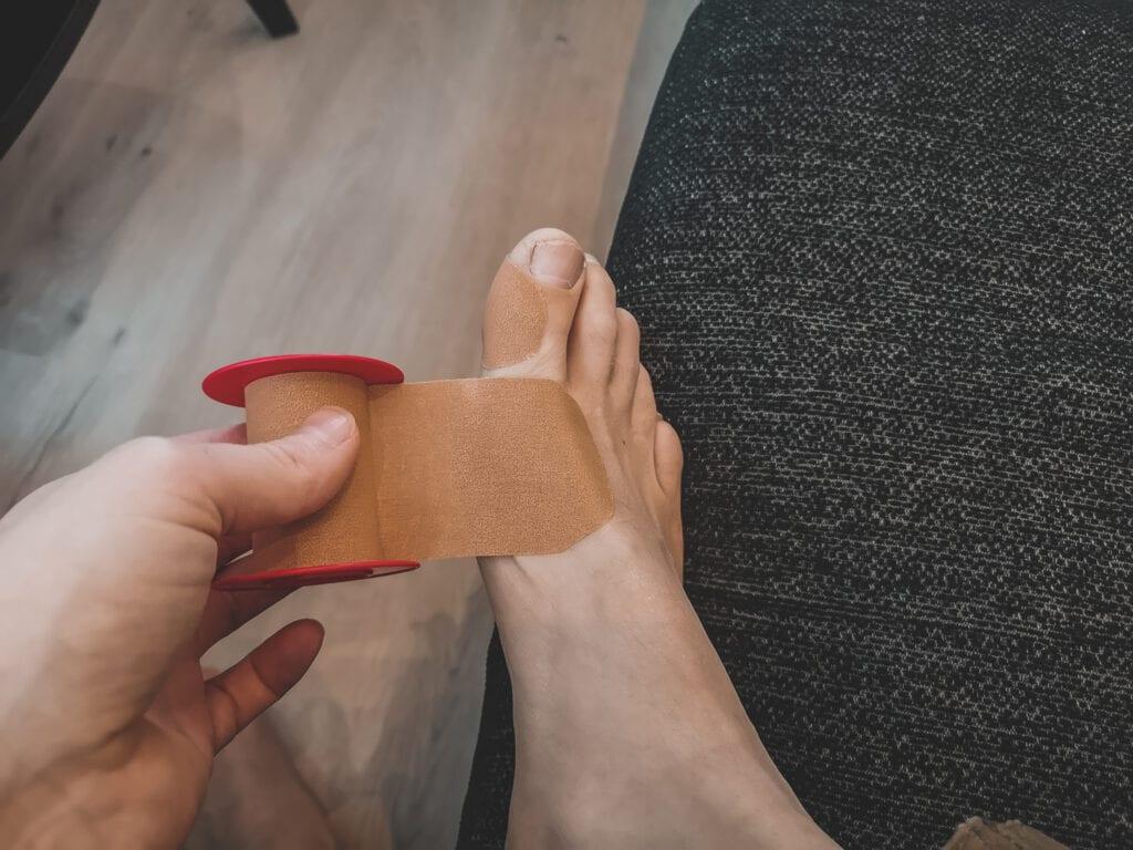 Slipp blåsor under foten och stortån med leukoplast
