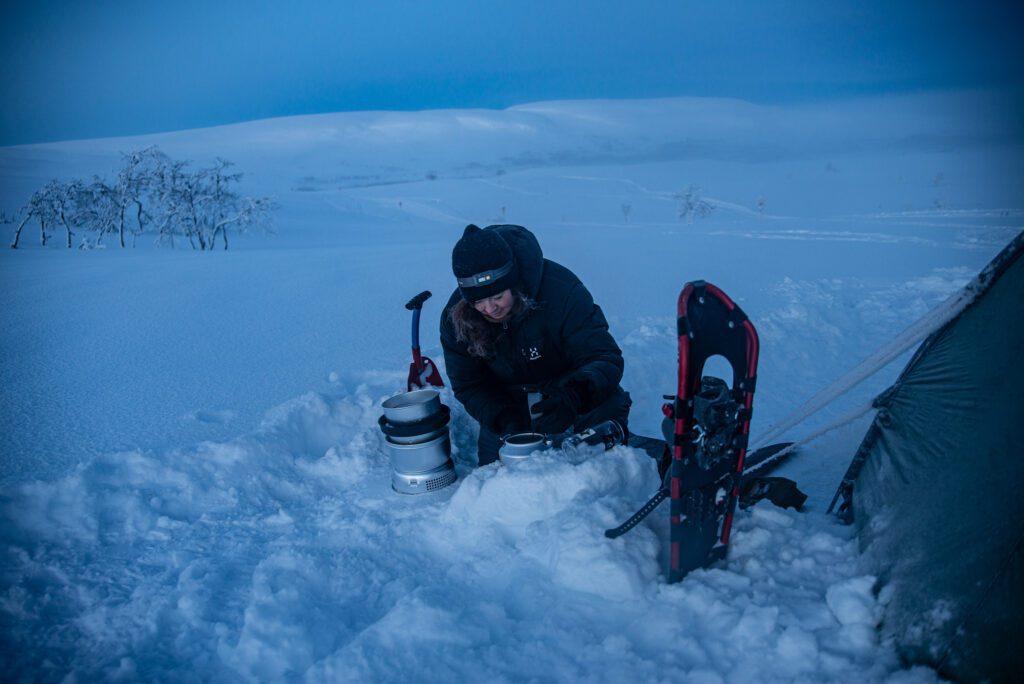 Koka kaffe på Trangia kök på vintern med tält bredvid